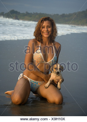 Portrait of a woman holding a dog on the beach - Stock Photo