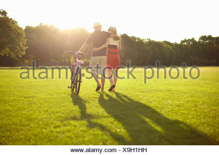 Couple strolling whilst pushing bicycle in park - Stock Photo