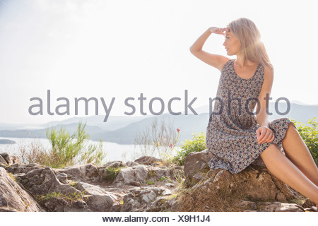 Young woman sitting on rocks shielding eyes - Stock Photo