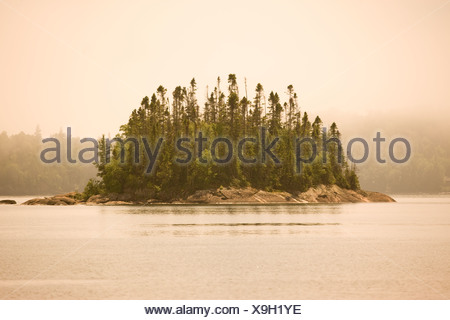 Island in fog in Warp Bay as seen from a canoe/kayak or hike-in campsite along Lake Superior Coastal Trail Lake Superior Provinc - Stock Photo