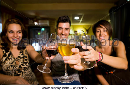 Three smiling friends in a bar clinking glasses - Stock Photo