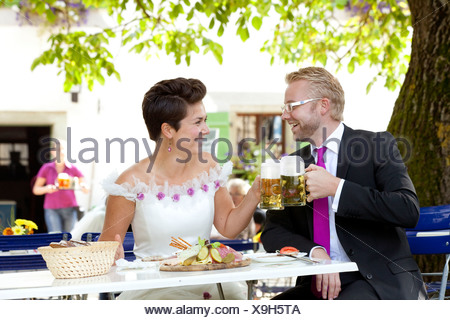 Bridal couple having a light meal and drinking beer in a Bavarian beer garden, Regensburg, Bavaria, Germany, Europe - Stock Photo