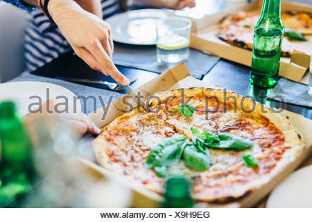 Hand cutting pizza in box on table - Stock Photo