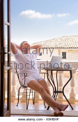 Man in boxer shorts relaxing on balcony next to laptop - Stock Photo
