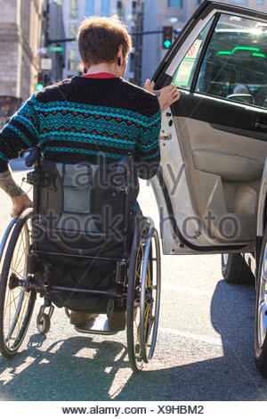 Trendy man with a spinal cord injury in wheelchair getting into a taxi cab - Stock Photo