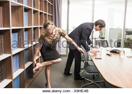 Woman putting on shoe and man leaning over table - Stock Photo