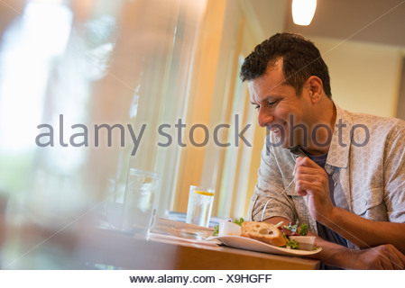 A man eating a snack in a cafe. - Stock Photo