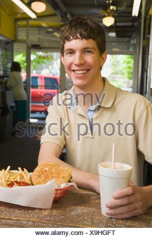 Teenage boy eating at fast food restaurant - Stock Photo
