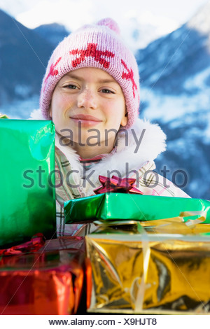 Portrait of girl with presents in snow - Stock Photo