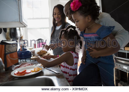 Young family making school lunches in kitchen - Stock Photo