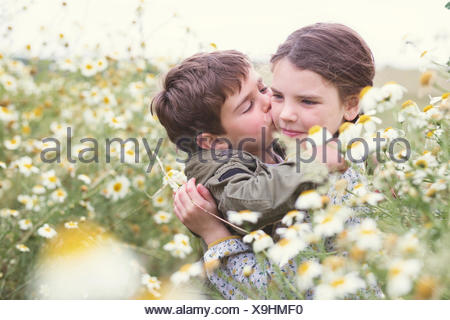 Boy kissing a girl's cheek in field of daisies, Andalucia, Spain - Stock Photo