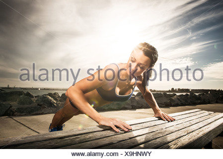 Woman doing push ups on park bench - Stock Photo