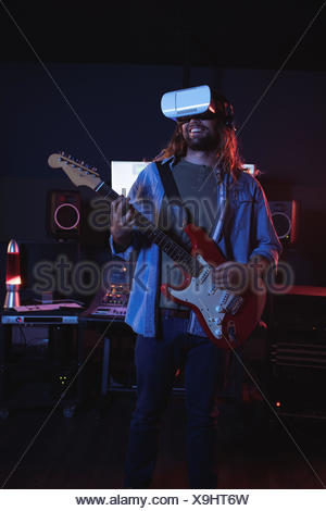 Male audio engineer using virtual reality headset while playing guitar in recording studio - Stock Photo