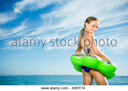 A young girl on the beach with rubber ring - Stock Photo