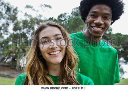 Portrait of beautiful young woman with male volunteer in park - Stock Photo