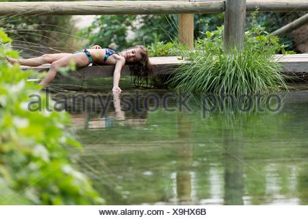 Girl lying on the footbridge of a lake. Take place in Bogarra, province of Albacete, Spain. - Stock Photo