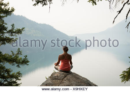 Fit woman sitting in meditating posture on the edge of a rock - Stock Photo