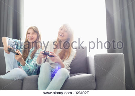 Sisters playing video games on sofa - Stock Photo