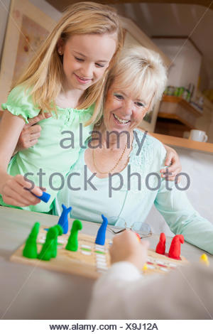 Girl playing board game with her grandmother, Bavaria, Germany - Stock Photo