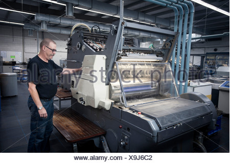 Worker operating print machine in printing workshop - Stock Photo