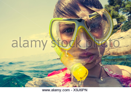 Croatia, Brac, Sumartin, Teenage girl in water with diving goggles and snorkel - Stock Photo