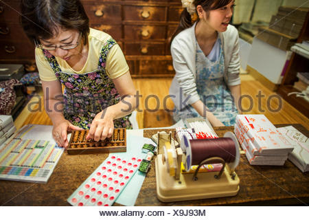 A small artisan producer of specialist treats, sweets called wagashi. Two women working packing sweet boxes for delivery. - Stock Photo
