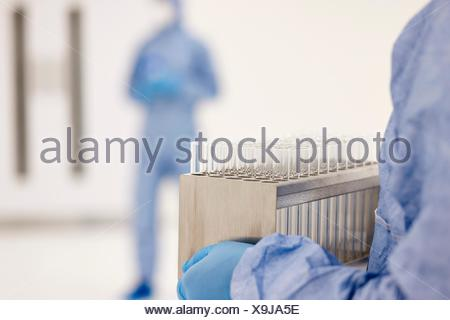 Scientist carrying tray of test tubes in laboratory - Stock Photo