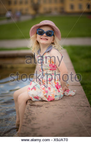 Girl sitting with her feet in water making a face - Stock Photo