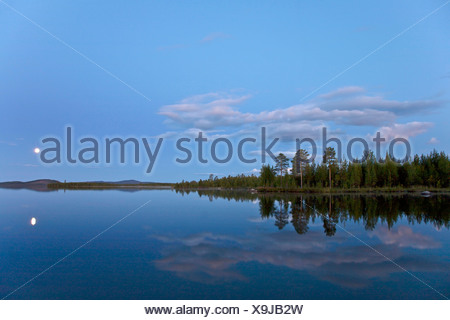 full moon mirroring in a lake in evening light, Sweden, Lapland, Norrbottens Laen, Kvikkjokk - Stock Photo
