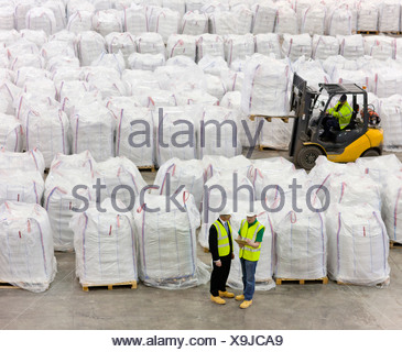 Businessman and workers among large bags of recycled plastic pellets in warehouse - Stock Photo