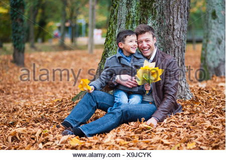 Young boy and father sitting in park with autumn leaves - Stock Photo