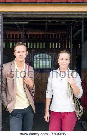 Sweden, Vastra Gotaland, Kungalv, Karna, Portrait of young man and woman in stable - Stock Photo