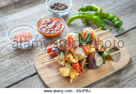 Grilled vegetable skewers on the wooden board - Stock Photo