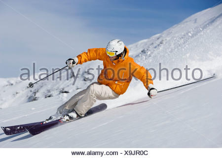 Skier carving through powder snow - Stock Photo