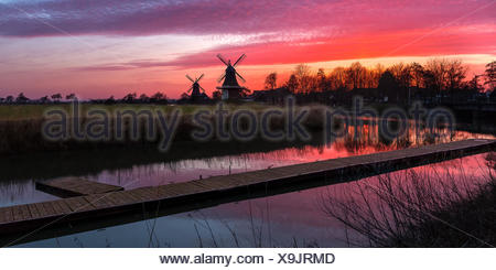 The famous twin mills of Greetsiel, East Frisia at sunrise - Stock Photo
