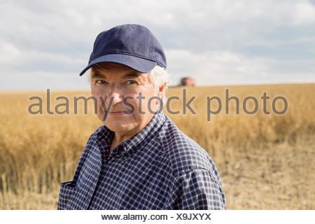 Portrait of confident farmer in sunny wheat field - Stock Photo