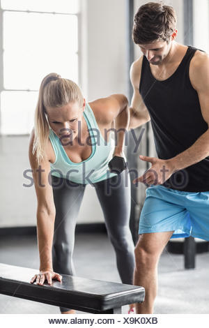 Sporty woman using dumbbells with personal trainor - Stock Photo