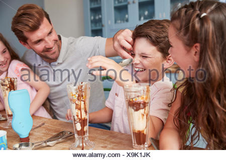 Father Making Ice Cream Sundaes With Children At Home - Stock Photo