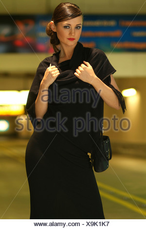 Young woman wearing black evening dress standing in front of the entrance to an underground garage (car park) - Stock Photo