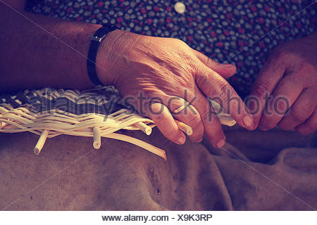 Close up of female hands weaving basket - Stock Photo