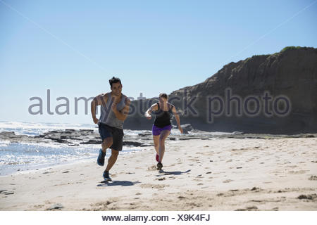 Man and woman running on sunny beach - Stock Photo