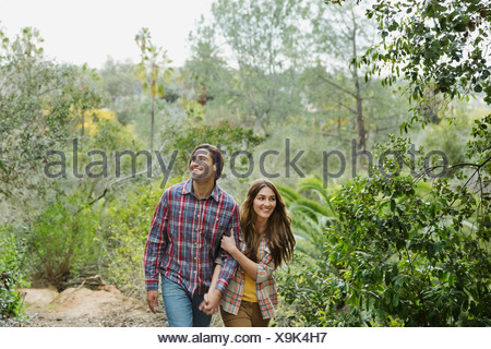 Happy young couple walking in forest - Stock Photo