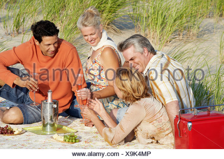 Two mature couples sitting on the beach and holding champagne flutes - Stock Photo
