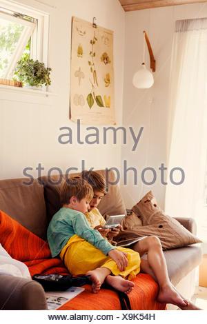 Sweden, Uppland, Runmaro, Barrskar, Brothers (4-5, 6-7) playing on game console on sofa - Stock Photo