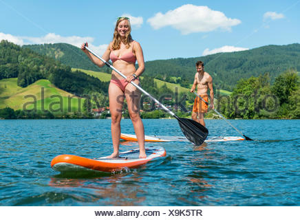 Young man and woman on paddle boards, using stand-up paddles, Lake Schliersee, Upper Bavaria, Bayern, Germany - Stock Photo