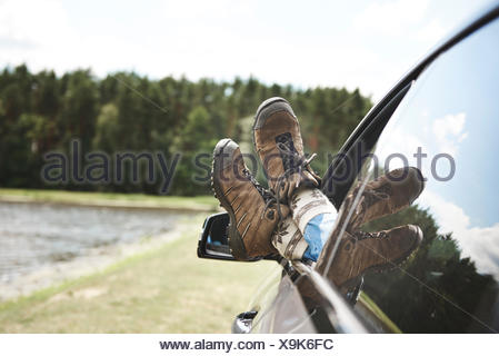 Woman relaxing in car, feet through open window, focus on feet - Stock Photo