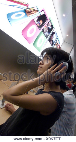 Chinese woman testing IPOD in Apple store, Beijing, China - Stock Photo