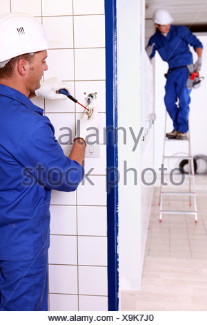 an electrician screwing an electrical outlet and a colleague on a stepladder - Stock Photo