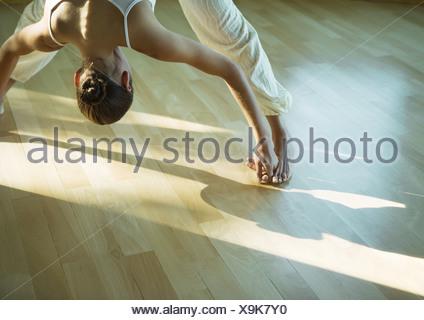 woman doing prasarita padottanasana yoga pose studio shot