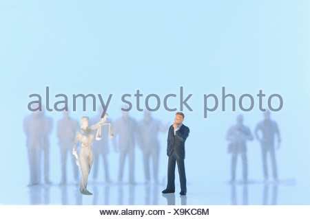 Figurine of justice and businessman on blue background - Stock Photo